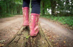 Kind balanciert im Wald auf Holz