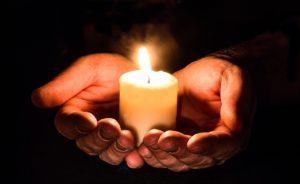 Kerze wird in Händen gehalten