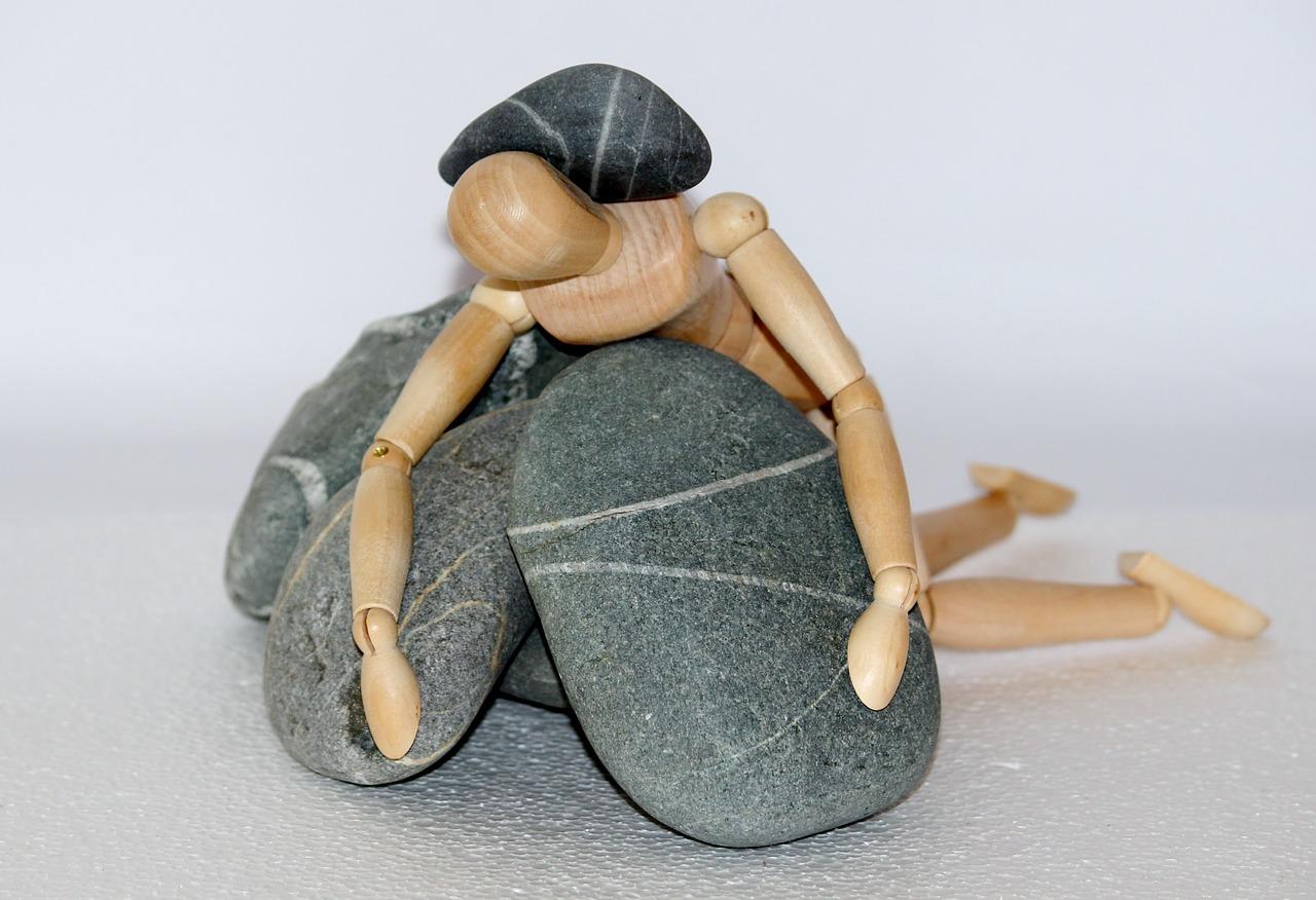 burnout, figur liegt zwischen steinen
