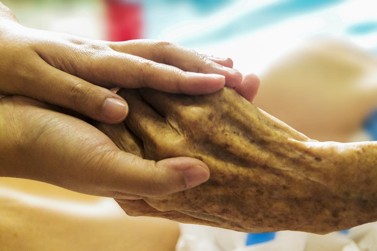 Jüngerer Mensch hält die Hand einer alten Person