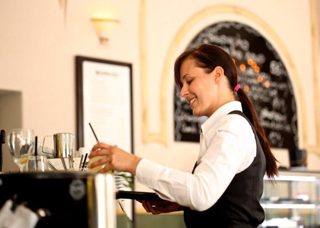 Junge Kellnerin steht an der Bar