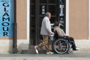 Mann schiebt Frau im Rollstuhl, Pflege.